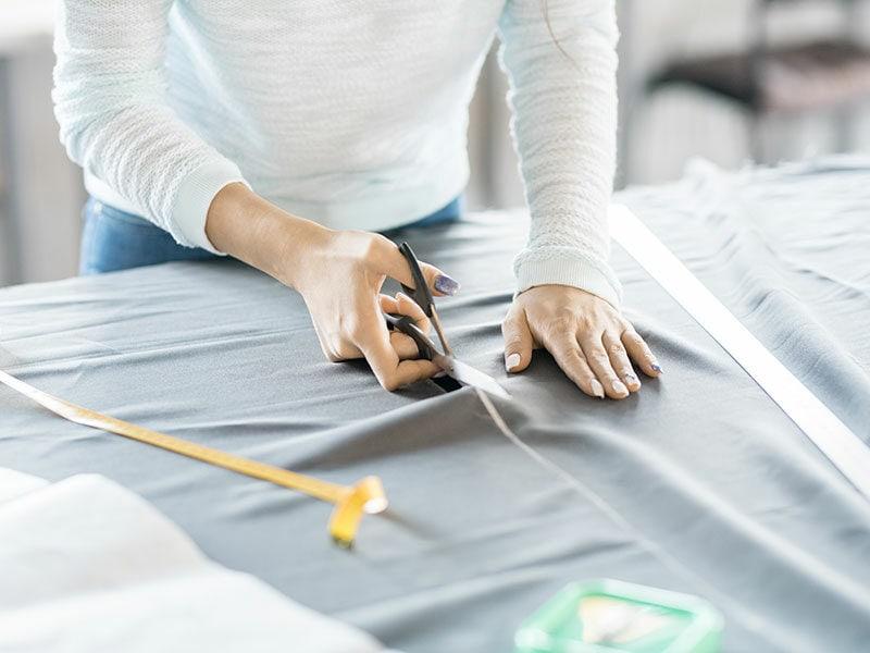 Female Tailor Cutting Fabric
